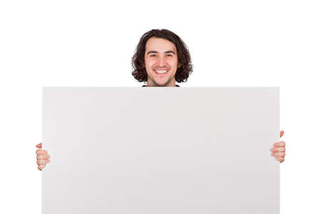 Contented young man holding a big blank banner for advertising. Happy guy with an empty sheet for text announcements isolated on white background with copy space. Marketing concept, positive message