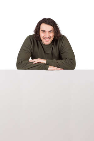 Contented young man, long curly hair style, keeps arms folded leaning on a blank whiteboard, looking confident to camera isolated on white background. Cheerful guy and copy space sheet for advertising