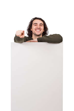 Joyful man standing behind a blank banner for advertising and messages. Happy guy pointing his forefinger showing to camera choosing you. Empty sheet, copy space for text announcements and marketing
