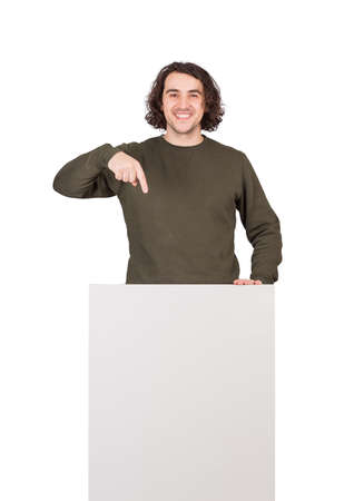 Positive man, lower body part hidden behind a blank banner for advertising and messages. Happy guy pointing his index finger to the empty sheet for text announcements. Male stands in front of rostrum 版權商用圖片