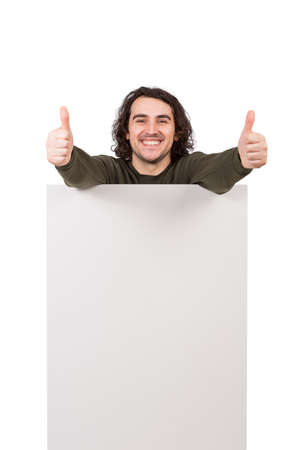 Contented man standing behind a blank banner for advertising and messages showing both thumbs up as positive feedback gesture. Empty sheet placard, copy space for text announcements and marketing