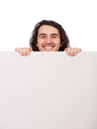 Closeup portrait, smiling man standing behind a blank banner for advertising and messages, looking cheerful to camera. Happy guy holding an empty sheet, copy space for text announcements and marketing