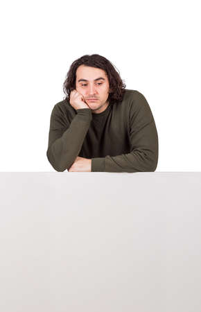 Pensive young man, long curly hair style, keeps hand under chin leaning on a blank whiteboard. Thoughtful casual guy and copy space banner for advertising. Thinking emotion male over white sheet