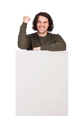 Pleased and passionate man celebrates success and achievement, standing behind a blank banner for advertising and messages. Empty sheet, copy space for text announcements. Happy male keeps fisting tight
