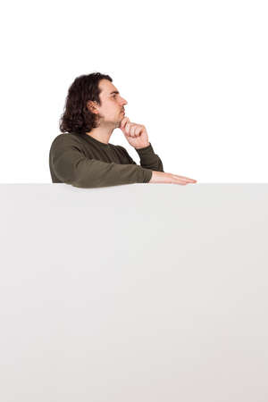 Side view of pondering young man, stands behind a blank banner, looks ahead thoughtful. Empty sheet with copy space for advertising and messages. Pensive and focused guy thinking with hand under chin