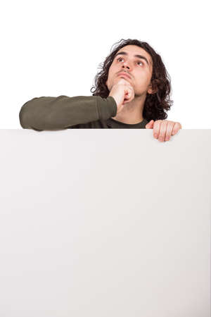 Pondering young man, stands behind a blank banner, looking up thoughtful. Empty sheet with copy space for advertising and messages. Pensive and focused guy thinking near whiteboard, hand under chin