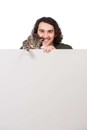 Cheerful young man hugging his cute cat pet, standing behind a blank banner for advertising and messages. Empty sheet, copy space for text announcements. Carefree and happy male, marketing concept