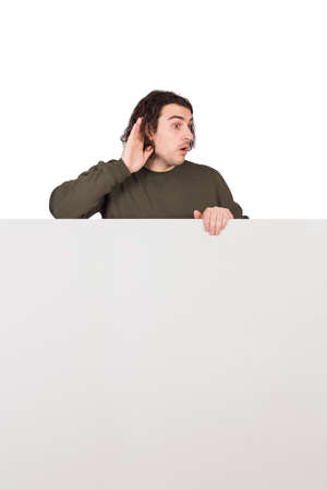 Curious man, hand to ear gesture, trying to listen to someone conversation, stands behind a blank banner as obstacle. Empty sheet with copy space for advertising and messages. Slanderer guy hear secrets