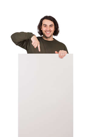 Positively surprised man pointing index finger to blank announcement banner, looking amazed to camera. Contented guy and empty sheet, copy space for promoting text and messages, marketing concept