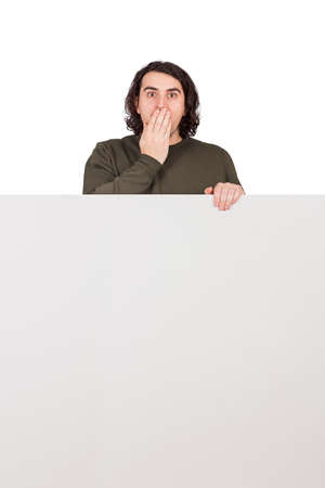 Shocked man, staring to camera with big eyes, covers his mouth with hand, stands behind a blank banner for announcements. Empty sheet with copy space for advertising and messages and astonished guy