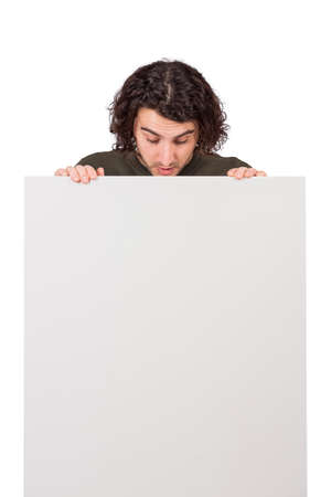Curious young man, long curly hair style, looks down as holds a blank banner for announcements. Thoughtful student guy with a copy space sheet for advertising and messages. Marketing concept