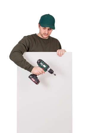 Young man with a screwdriver or electric drill in his hand, stands behind a white panel. Renovation worker before installing interior finish plate or assembling DIY furniture using drilling power tool