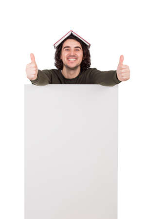 Excited young man, with a book on his head, shows thumbs up gesture, standing behind a blank announcement banner. Joyful guy looks positive expression. Empty advertising placard with copy space 版權商用圖片