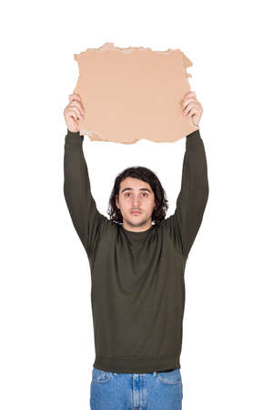 Man with hands outstretched holding a blank cardboard sheet over head as participates in a street demonstration or protest. Blank banner for advertising and messages. Person isolated on white 版權商用圖片