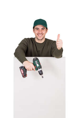 Positive renovation worker with a screwdriver or electric drill in his hand, stands behind a white panel, shows thumb up gesture. Man installing interior finish plate or assembling DIY furniture.
