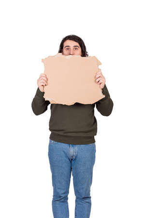 Stressed man, refugee or beggar, holding a blank cardboard sheet, copy space for messages. Empty banner for advertising. Homeless unemployment and poverty concept. Homelessness as social issue