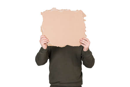 Anonymous man covers his head with a blank cardboard sheet, copy space for messages. Empty banner for advertising. Incognito person hidden, isolated on white background. Introvert people hiding face