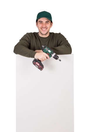 Friendly maintenance worker with a screwdriver or electric drill in his hand, stands behind a white panel. Man installing interior finish plate or assembling DIY furniture using drilling power tool
