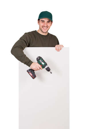 Smiling man with a screwdriver or electric drill in his hand, stands behind a white panel. Renovation worker before installing interior finish plate or assembling DIY furniture using drilling power tool