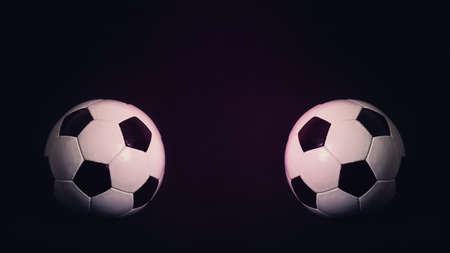 Two classic soccer balls, one in front another, isolated on a black background with copy space for match announcements and advertising. Traditional football playing ball. Tournament rivalry concept
