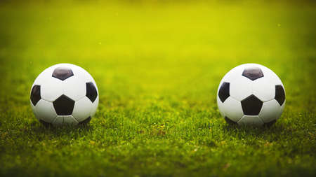 Two classic soccer balls, one in front another, placed on the green grass stadium turf. Traditional football playing ball on natural lawn with copy space for match announcements. Tournament rivalry