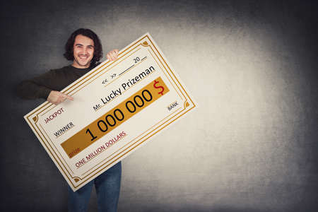 Excited man holding a lottery winner bank check. Happy jackpot guy winning one million dollars prize. Big banner announcing the main award. Wealth, luck and success concept. Becoming a millionaire Standard-Bild