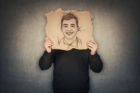 Anonymous man covers his head with a fake mask, hiding emotions behind a torn cardboard sheet with another face expression sketch drawing. Incognito person wanted. Introvert person, hidden identity Standard-Bild
