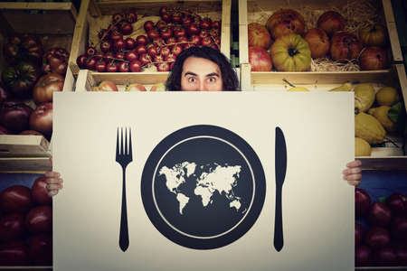 Global hunger, food supply issue. Shocked man holding a warning message banner in front of a grocery store. World map in a plate with knife and fork. International starvation, famine after drought Standard-Bild