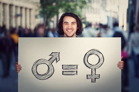 Gender equality concept as young man holding a big banner with male and female symbol, as protest demonstration message on a crowded city street. Sex rights and discrimination as a major social issue