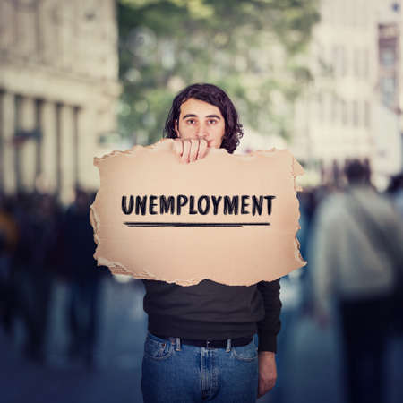 Unemployment as global issue. Unemployed man activist holding a cardboard banner, participating in a street demonstration protest. Social problem, lack of economic opportunity, struggle for workplace Standard-Bild