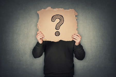Anonymous man covers his head using a torn cardboard sheet, like a mask, with drawn question mark. Incognito person hidden, isolated on gray wall background. Introvert people hiding identity