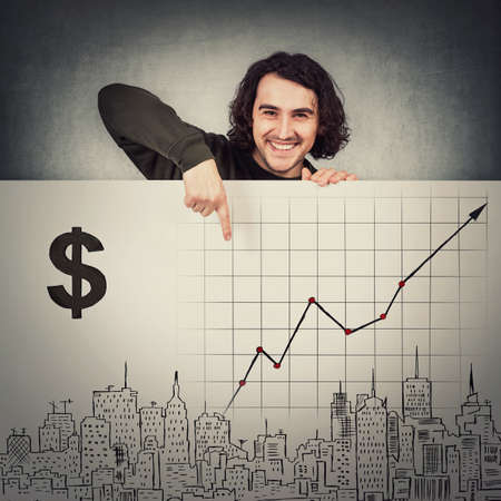 Contented man standing behind a whiteboard with economic sketches, pointing index finger to a growing financial graph. Real estate marketing concept. Business plans and prognosis, increasing incomes Standard-Bild