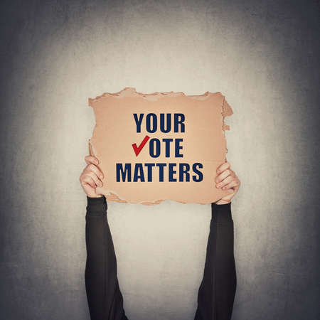 Activist hands holding up a cardboard banner with text message your vote matters, isolated on gray wall background. People legal and democratic rights, every voice counts. Election campaign agitation Standard-Bild