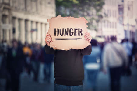 Anonymous man covers his head using a torn cardboard banner with hunger text message. Incognito person on a crowded street as protest demonstration against global famine. Food supply issue