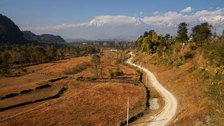 visually: A dirt road visually leading to Mount Machapuchare, Annapurna region of Himalayas. Machapuchare(Fishtail) has never been climbed to the top.