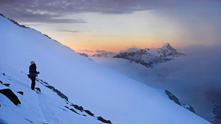 Alpes: A girl is staring at the sunset over the clouds. View from Grossglockner peak, Alpes. Stock Photo