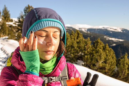 Woman in a winter mountain putting sunsceen on her face.