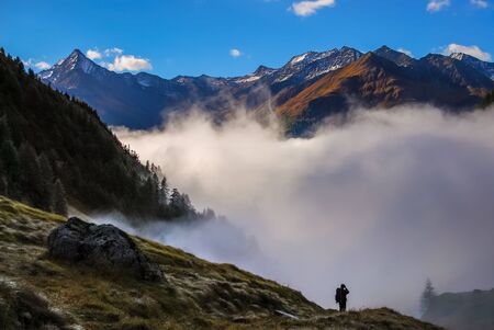 admires: A man admires the sunny mountain. The lower valley is full of clouds. Stock Photo