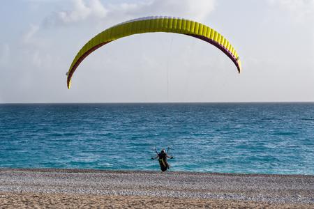 paraglider: Paraglider landing on a beach. Oludeniz, Turkey.