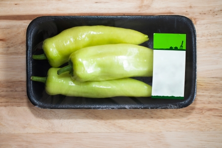 Green Sweet Pepper wrapped in package on wood table
