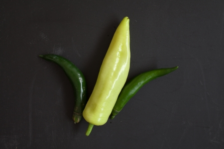 Green Sweet Pepper arrange like a corn on Black Chopping Block Stock Photo