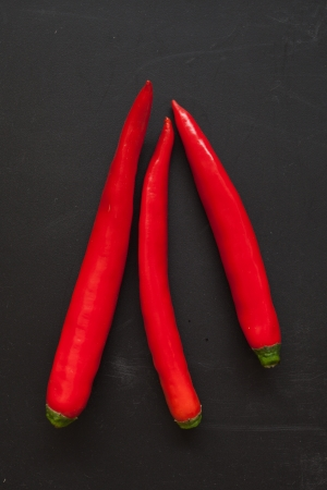 Red Chilli Pepper on Black Chopping Block Stock Photo