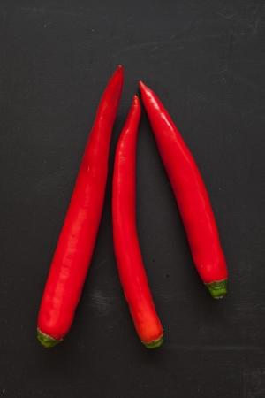 Red Chilli Pepper on Black Chopping Block Stock Photo