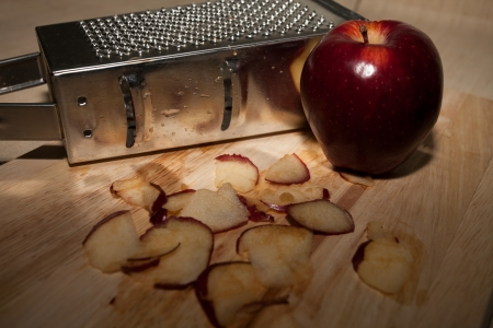 Smiley Metal grater and apple on cutting board