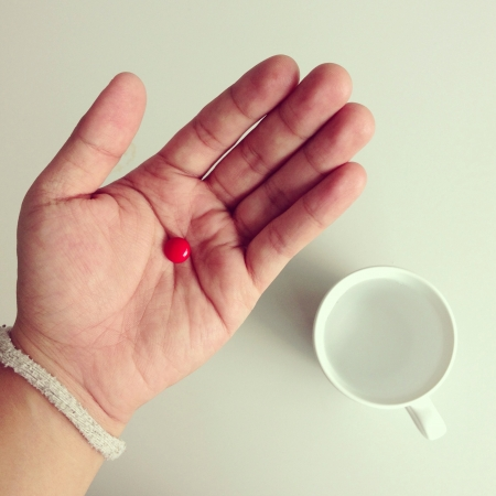 Red pill in hand  Stock Photo