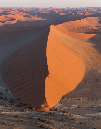 View from a helicopter of one of the large red sand dunes of Sossusvlei in Namibia