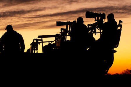 Wildlife photographers on a photo tour in south Africa sitting on a game drive vehicle jeep at sunset