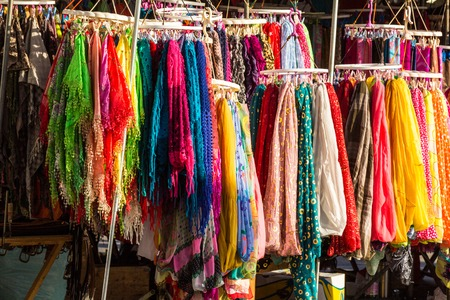 A bunch of bright colored shawls on display at a market