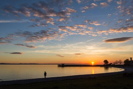 Soft light and a lonely figure at lake constance