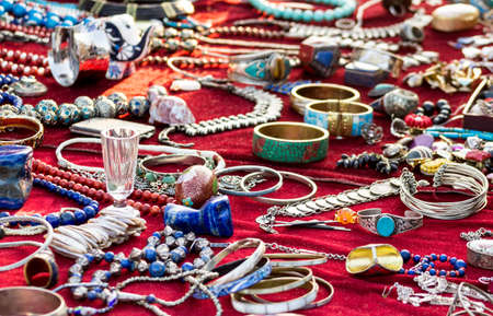 Necklaces, bracelets and semicprecious stones on a red table.